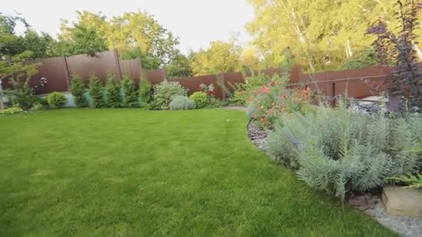 Gyönyörű kert gyeppel és dísznövényekkel. Panoráma egy vidéki ház telek gyönyörű növények és a gyep.