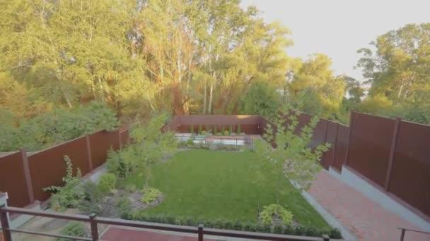 Vidéki ház, gyönyörű növényekkel és gyeppel. Gyönyörű kert gyeppel és dísznövényekkel