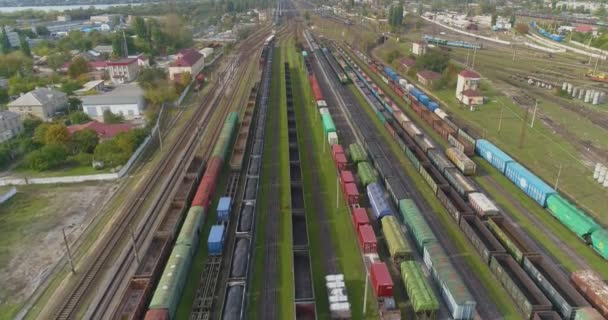 Trains are parked at the depot at the railway junction. Many colored trains. Large industrial railway depot.