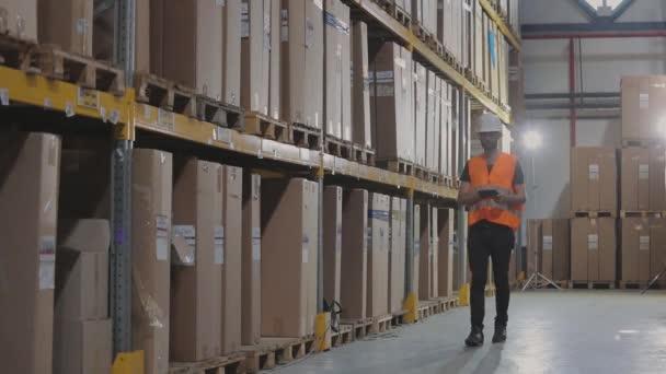Egy menedzser egy táblagéppel a raktárban ellenőrzi az árut. Egy nagy gyár raktárvezetője.