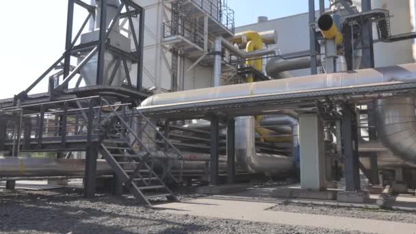 Es gibt viele große glänzende Rohre in der Fabrik. Große, metallisch glänzende Rohre. Industrieaußenbereich