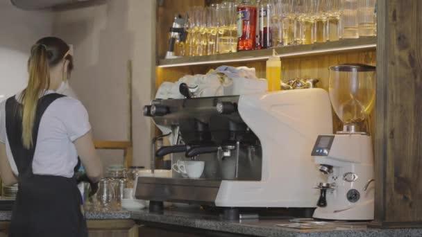 Egy fiatal barista kávét főz. Kávét főzni egy elegáns kávézóban