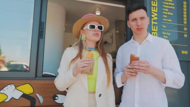 Veselí mladí lidé jedí hot dog. Stylový chlap s dívkou jíst hot dog