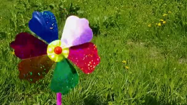 Kinderwindmühle auf einem Hintergrund aus grünem Gras. Kinder bunte Windmühle