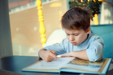 Boring and tired little boy reading book
