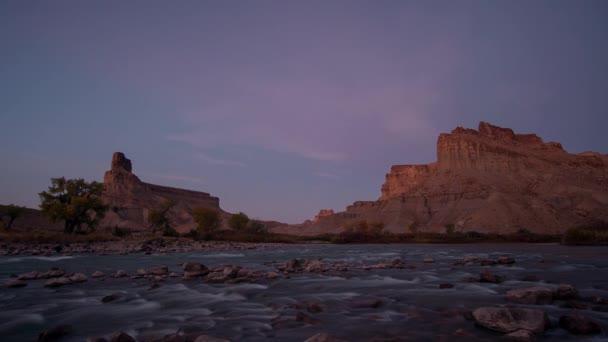 Čas východu slunce ubíhá nad Zelenou řekou v poušti Utah od pláže Swaseys, když se rozsvítí útesy.