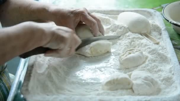 Old women cuts the dough for making pasta