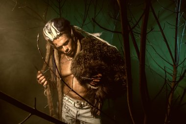 Muscular man with dreadlocks and skin through the trees and mist
