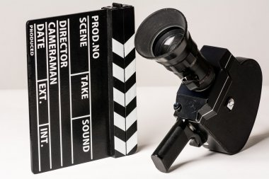 Old movie camera with film clapperboard.