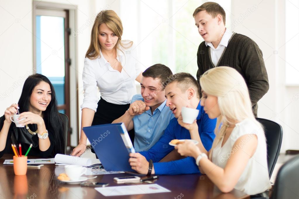 En grupp unga affärsmän på kontoret har kul att diskutera problemet.  Studenter vid bordet — Foto av kanzefar d213c3fc0f658