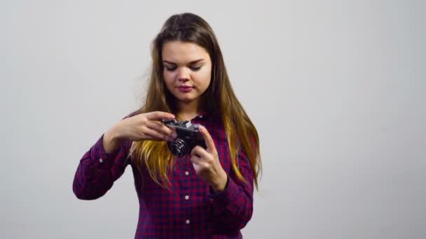 fiatal lány használja a régi film kamera fehér háttér előtt
