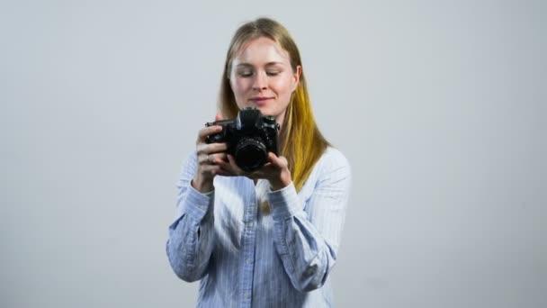 mosolygó fiatal lány bevétel mozi-val egy kamera előtt fehér fal