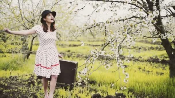 mladá žena oblečená v retro stylu pózuje v zpomalené kvetoucí zahrady