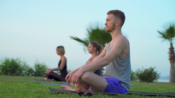 csoport ember csinál a légzési gyakorlatot ül a fűben