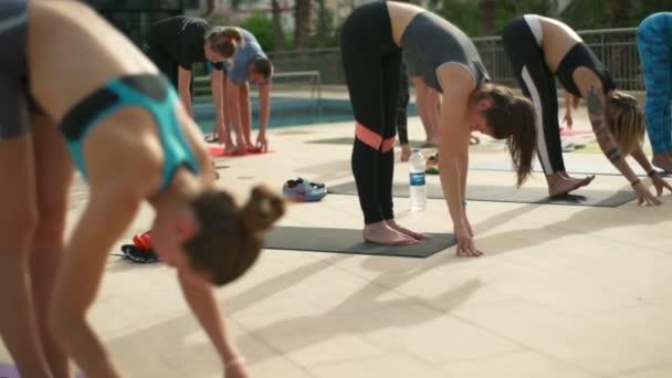 Gruppe von Menschen, die Yoga in der Nähe des Pools in Zeitlupe praktizieren