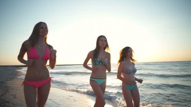 čelní pohled dívky v bikinách podél moře na východ zpomalené