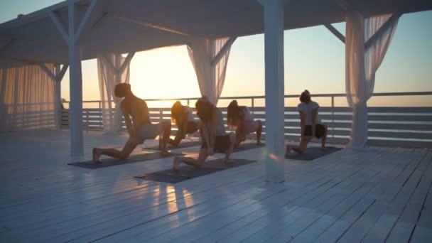 a teraszon a tenger jógázhatnak a dawn lassított emberek csoportja