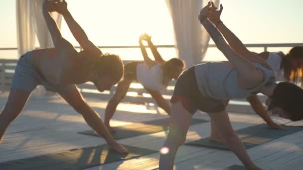 az emberek gyakorlat jóga: dawn lassított teraszon csoport