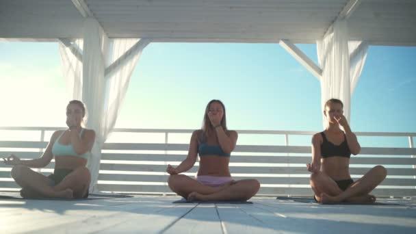 három nő, meditáció és a légzés során a terasz lassított jóga