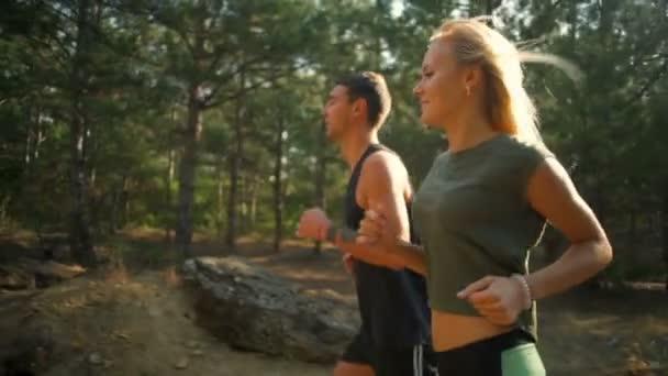 Nádherný sportovní pár usmívá, běhání v lese zpomalené profil zobrazení