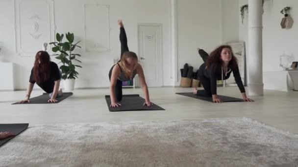 mladé pohledné feny dělá jógu ve velkém studiu pokoj s instruktorem