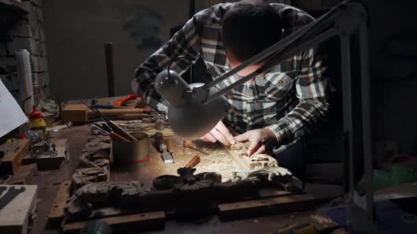 Attractive adult male working with wood frame in his own workshop