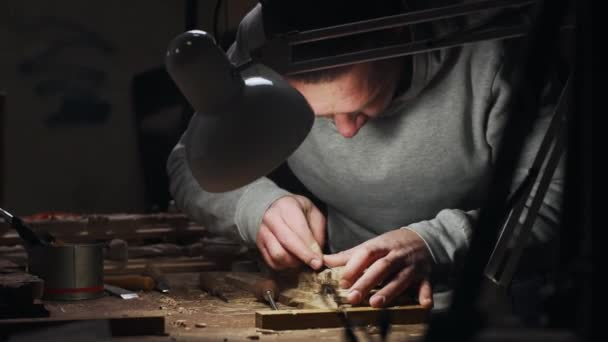 Young adult male joiner working with wood frame in his own workshop