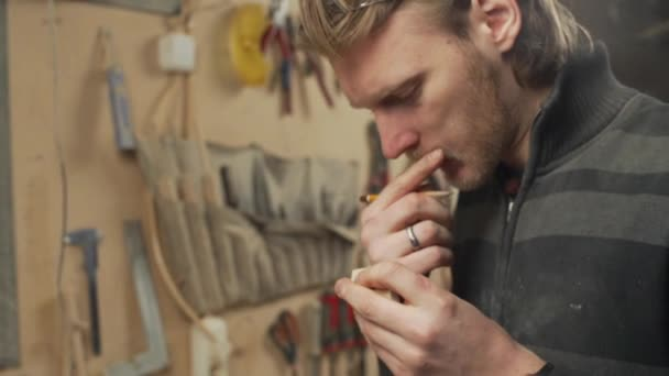 mladý pohledný truhlář kreslení na dřevěné části ve své dílně zpomalený pohyb