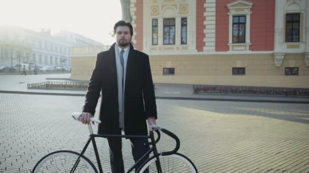 pohledný podnikatel, stojící na náměstí u jízdního kola