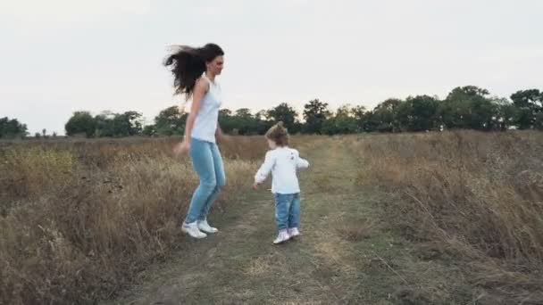 skákat radostí matka a dcera na podzimní pole