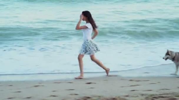 süße junge Frauen spielen mit zwei husky Hunde am Strand