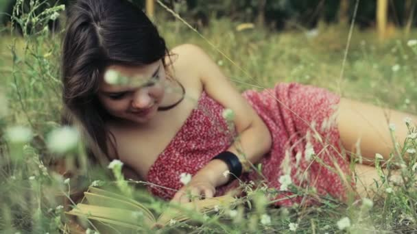 young woman lays in field flowers and reads a book slow motion