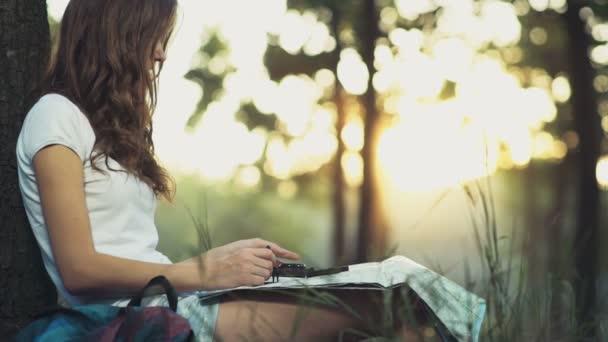 mladá žena s mapou a kompasem v lese zpomalené