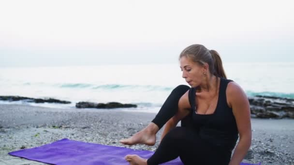 young female practices yoga on the beach slow motion