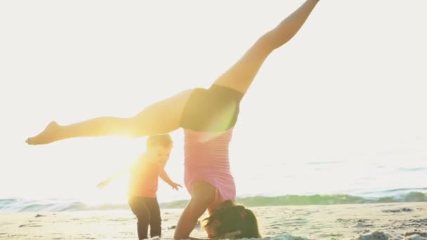 mother does gymnastics with her child on the beach slow motion