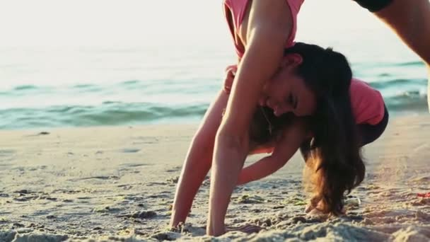 mother and her child do gymnastics on the beach slow motion