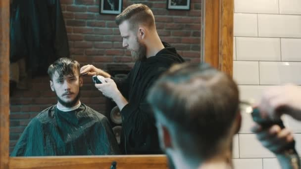 Barber cuts the hair of the client with clipper