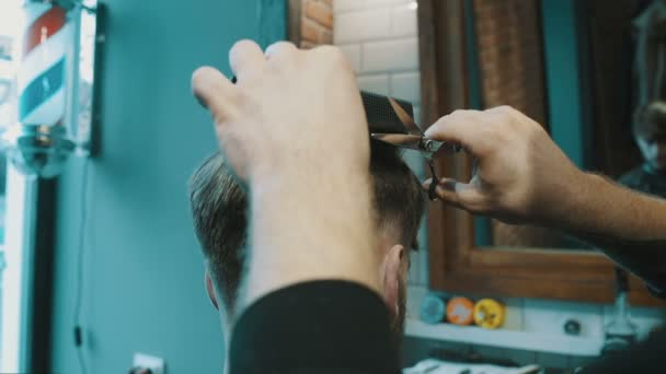 Barber cuts the hair of the client with scissors