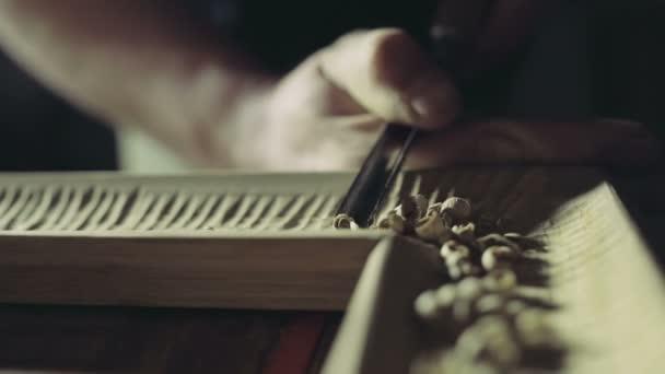 truhlář činí zářezy na dřevěné dílu s zahnuté dláto