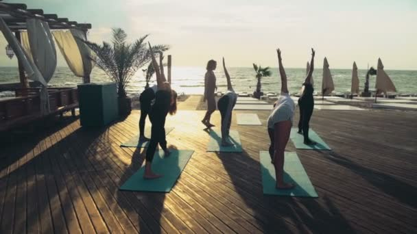 group of women practicing yoga on the beach slow motion