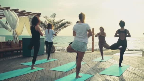 Gruppe von Frauen praktiziert Yoga am Strand Zeitlupe