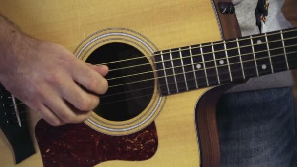 Nahaufnahme eines Mannes, der die akustische Gitarre in Zeitlupe spielt