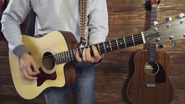 close up man strumming on acoustic guitar slow motion