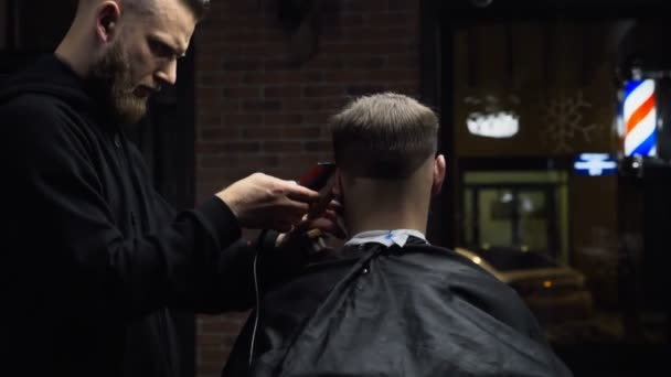 Barber cuts the hair of the client with trimmer slow motion