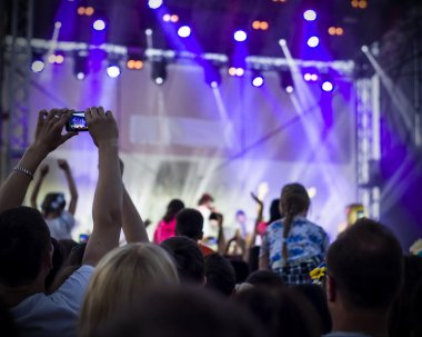 Photo of young people having fun at rock concert, active lifestyle,