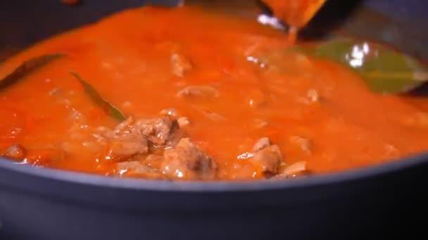 domácí chutné dušené maso v rajčatové omáčce se zeleninou. guláš v misce, vaření.