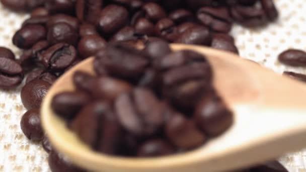 kávová zrna zblízka nalije dřevěnou lžíci. selektivní zaměření