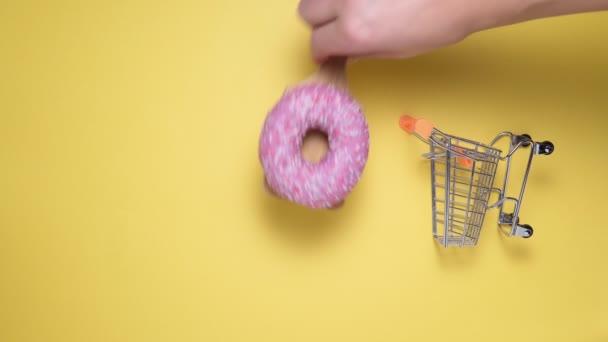koblihy s růžovou na žlutém pozadí. Ležel. kopírovací prostor kupuje sladkosti. vertikální video