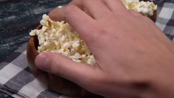 popcorn v kulaté dřevěné mísy na černém pozadí textury, film noční svačinka