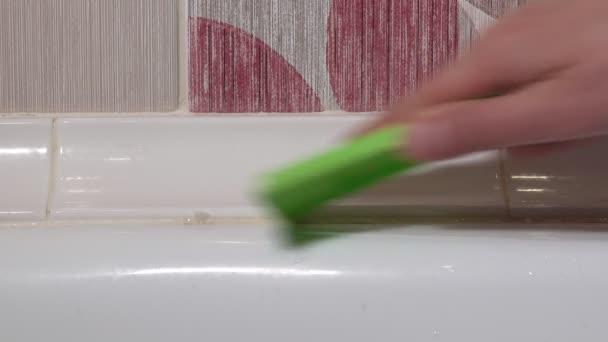 odstraňuje starý silikonový tmel v koupelně. selektivní zaměření